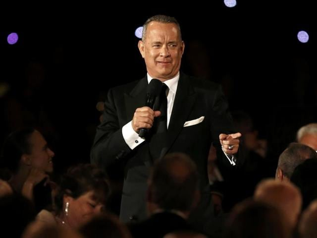 Actor Tom Hanks speaks while standing amid the audience at the 8th Annual Governors Awards in Los Angeles.