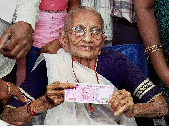 Prime Minister Narendra Modi's mother Heeraben Modi shows the 2000 rupees note after exchanging the old 500 and 1000-rupee notes at a bank in Gandhinagar on Tuesday.