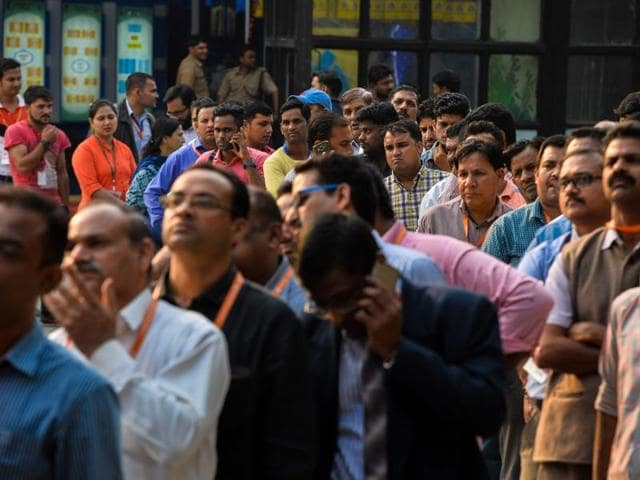 People wait in a queue to withdraw money from a mobile ATM machine in New Delhi on November 15.