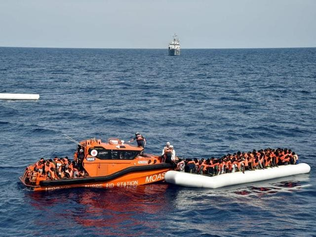 Migrants and refugees on a rubber boat wait to be evacuated during a rescue operation by the crew of the Topaz Responder, a rescue ship run by Maltese NGO