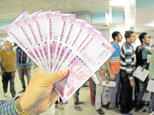 A bank officer shows new Rs 2000 notes in a bank in Jammu on Sunday.