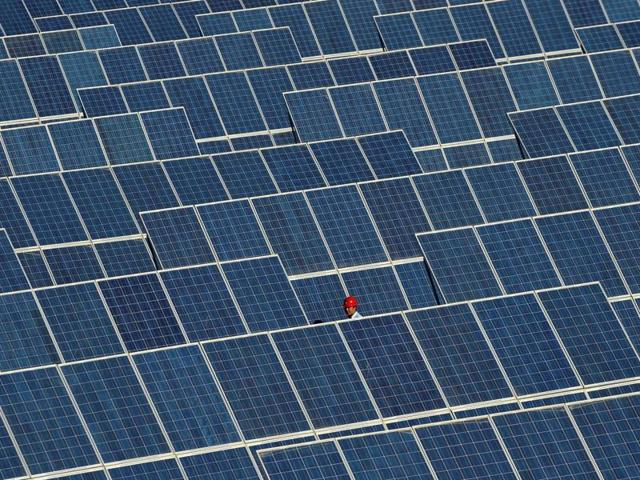 An employee walks between rows of solar panels at a solar power plant on the outskirts of Dunhuang, Gansu province, China.
