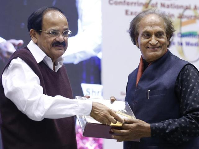 Renowned Indian photographer Raghu Rai, right, receives an award from Union Minister of Urban Development, Housing and Urban Poverty Alleviation and Information & Broadcasting, Venkaiah Naidu at the National Awards for Excellence in Journalism, in New Delhi.