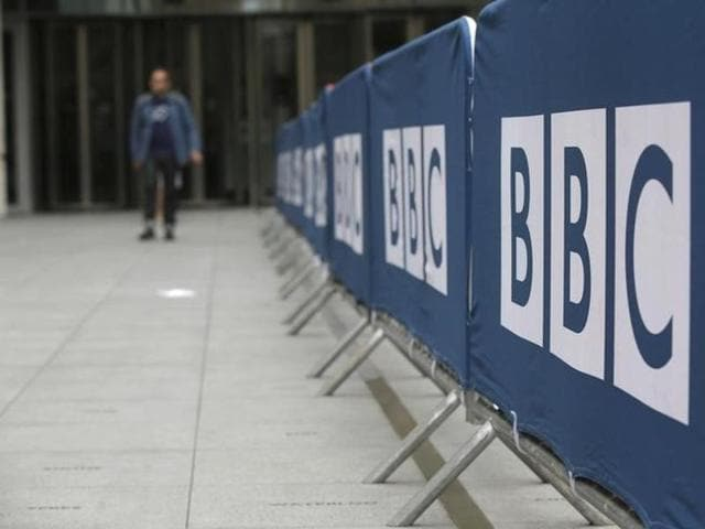 File photo of a pedestrian walking past a BBC logo at Broadcasting House in central London.