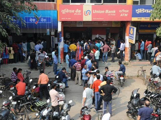 People standing in a long queue outside banks in Gurgaon.