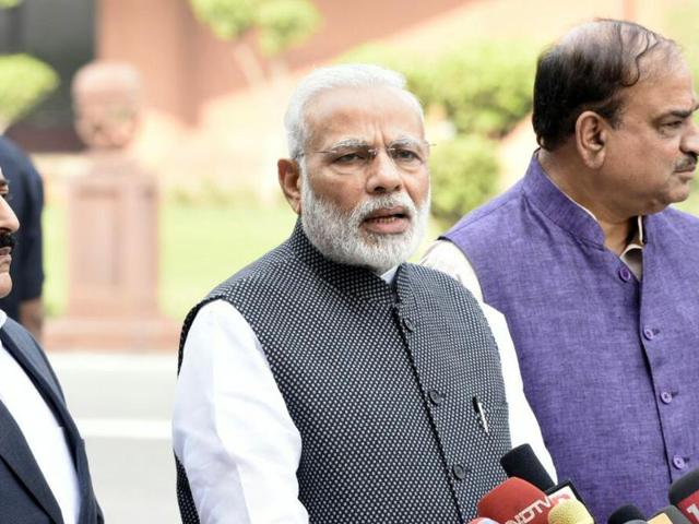 Prime Minister Narendra Modi with others ministers taking to media person on his arrival to attend the Parliament winter session in New Delhi on Wednesday