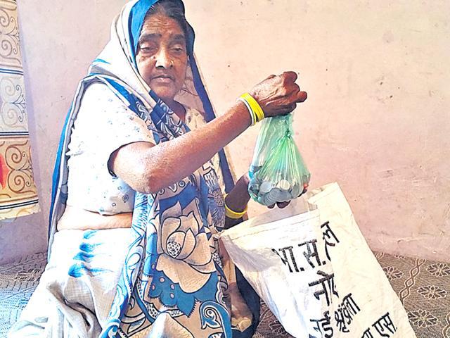 Sarju Devi shows the bag containing Re 1 coins.