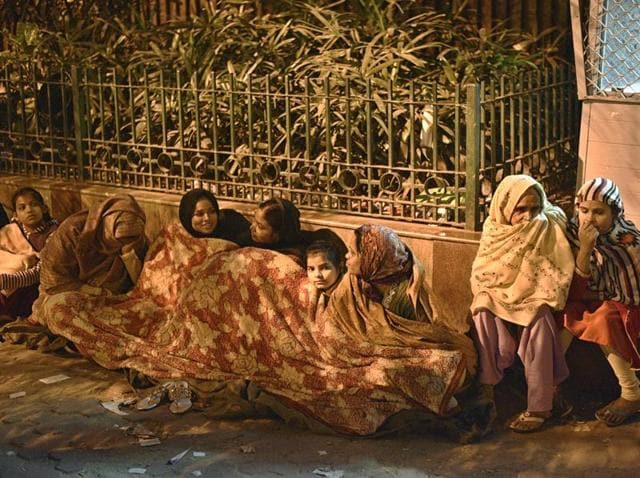 People sleep outside Reserve Bank of India as they wait to exchange their old notes on Thursday.