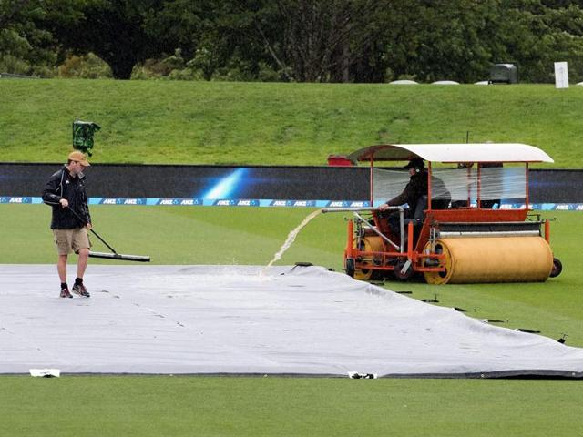 Grounds staff dry the wet grounds as rain delays the start of day one of the first cricket Test match.