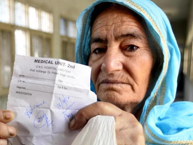 A patient's wife showing a slip given by a medical store owner with balance amount written on it in Amritsar on Wednesday.
