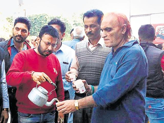 AAP candidate from Sham Churasi Ravjot Singh serving tea to people outside a bank in Hoshiarpur on Wednesday.