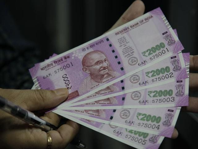 A man shows new Rs 2000 banknotes he received after exchanging discontinued currency notes in Jammu.