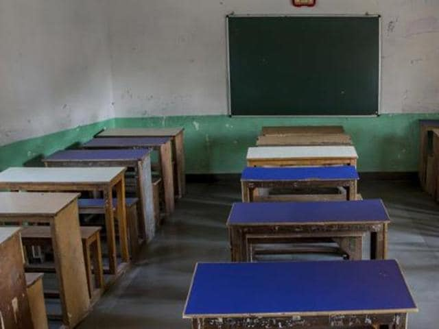 In this Oct. 18, 2016 photo, desks and benches stand in a row inside an empty classroom of a private school that remained closed for three months in Srinagar.