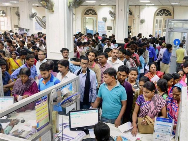 People stand in queues to withdraw money and exchange old currency notes in a bank in Allahabad on Wednesday.