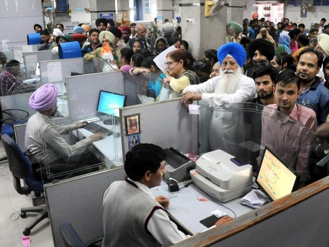 People stand in queues in a bank to deposit Rs 1000 and Rs 500 currency notes in Amritsar.