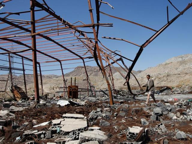 A man walks outside at a waste recycling factory which has been recently hit by Saudi-led air strikes on the outskirts of Sanaa, Yemen.