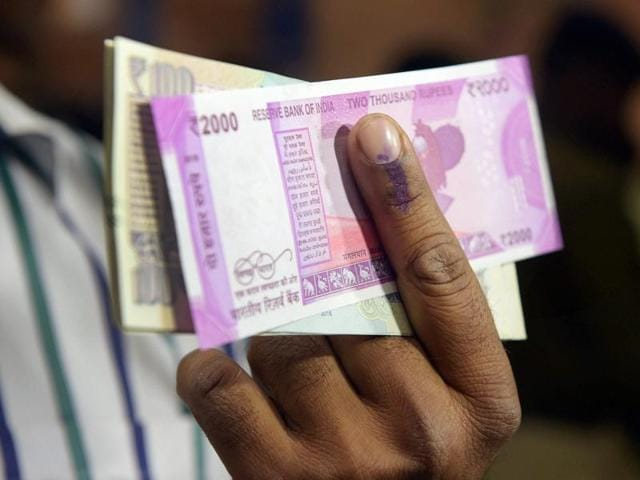A bank employee applies ink to a customer's finger after exchanging Rs 500 and Rs 1000 rupee currency notes at a SBI branch in New Delhi on Wednesday.