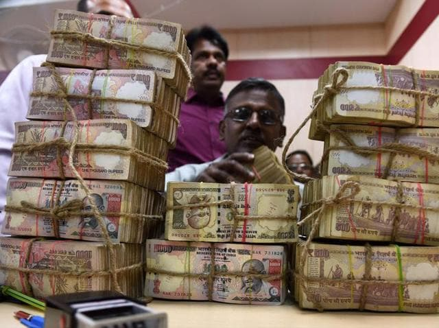 A bank employee counting the bundles of the received currency of old Rs 500 and 100 notes at cash counter at a Punjab National Bank branch in Chennai on Wednesday.