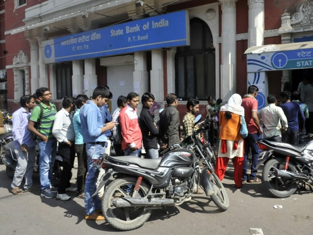 People wait outside an ATM in Indore.