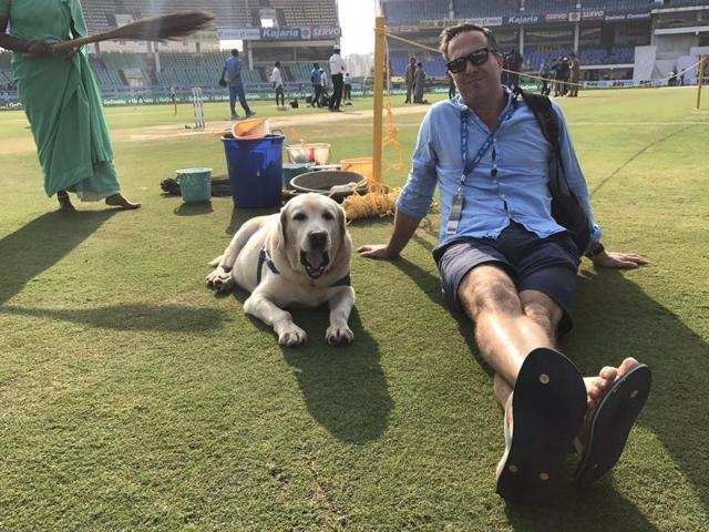 England's captain Alastair Cook, left, and team mate Jonny Bairstow watch the dog running into the field on Day 1 of the India vs England Test in Visakhapatnam.