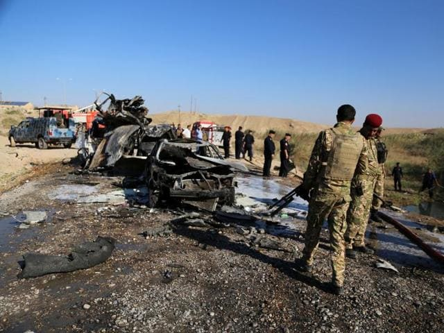 Iraqi security forces inspect the site of a blast where a suicide bomber detonated his explosives-laden ambulance at the southern entrance to the city of Tikrit, Iraq on November 6.