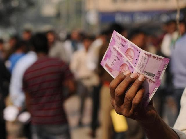 People take photos with the new Rs 2000 notes after exchanging it at a bank in Noida, Uttar Pradesh.