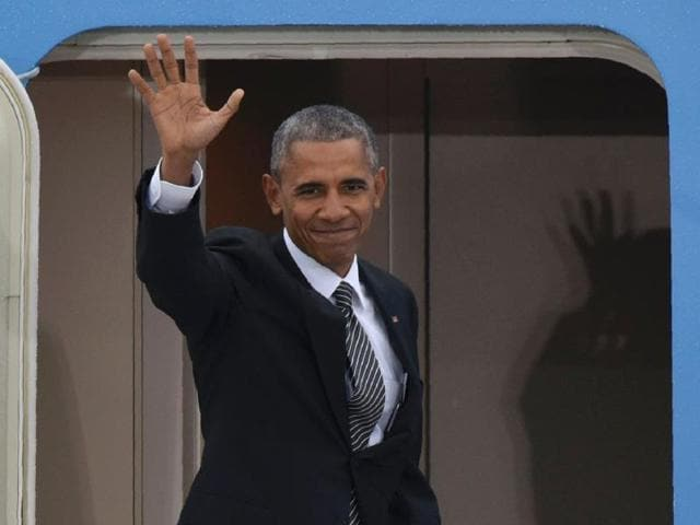 US President Barack Obama waves as he enters his plane
