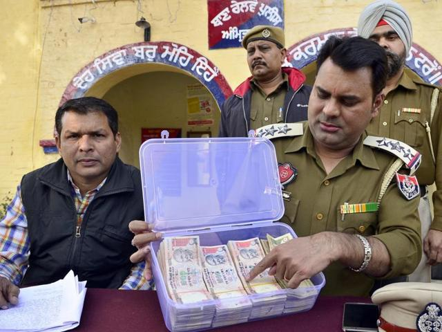 GRP's Amritsar SHO inspector Dharminder Kalyaan along other officials showing the seized currency in Amritsar on Friday.
