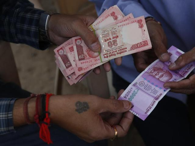 A man gets a Rs 2000 banknote exchanged for smaller notes at a roadside stall, in Ahmadabad.
