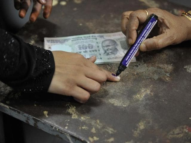 A woman has her finger inked with indelible ink after exchanging old denomination Rs 500 and Rs 1000 currency notes at a head post office in Hyderabad on November 18.