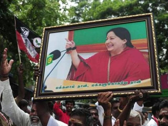 Members of the AIADMK party carry placards with the image of party leader Jayalalithaa.