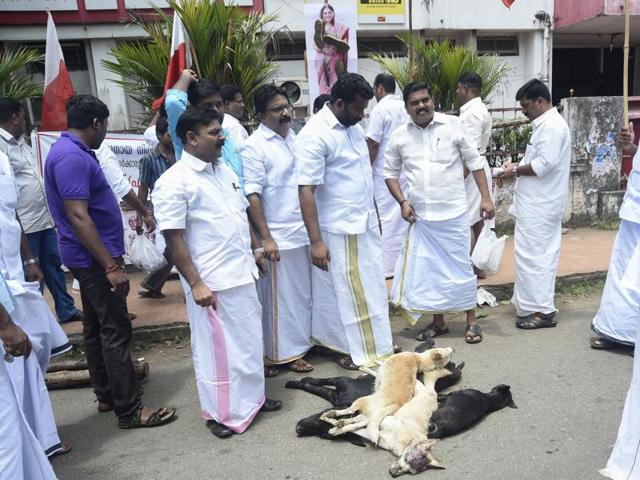 People stand next to the bodies of dogs as they protest against dangerous strays in Kerala's Kottayam.