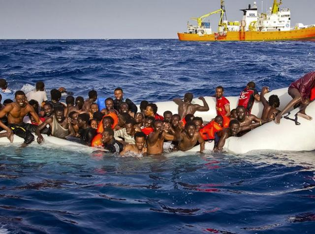 In this file photo taken on Sunday, April 17, 2016 migrants ask for help from a dinghy boat as they are approached by the SOS Mediterranee's ship Aquarius, background, off the coast of the Italian island of Lampedusa. About 365 migrants have died or gone missing in Mediterranean Sea shipwrecks.