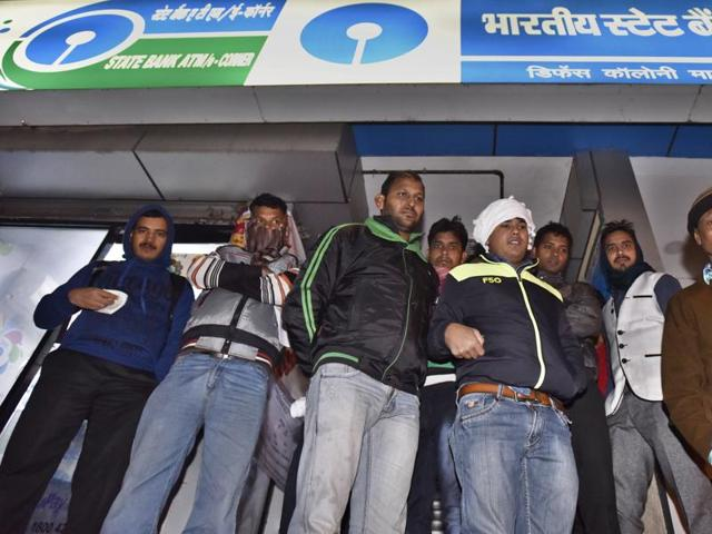 People wait outside an SBI branch in New Delhi on Friday.