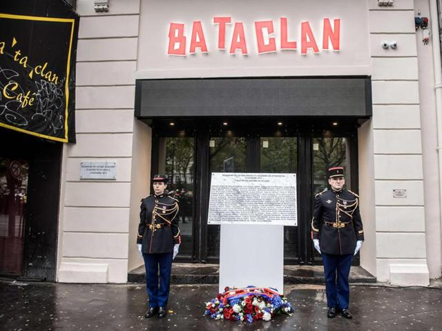 French Republican Guards stand next to a commemorative plaque at the Bataclan concert hall in Paris on November 13, 2016.