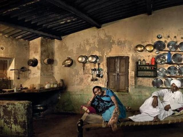 Sarpanch's Home, Karan Ismailpura, Gujarat. Champaben Prajapati is Ismailpur's first woman pradhan. Her posture in this photograph seems to reflect the confidence her council position provides. Champaben's husband Hargovan, since deceased, was a farmer and vice pradhan of the panchayat. The multitude of steel utensils lining their walls testify to the family's relative prosperity.