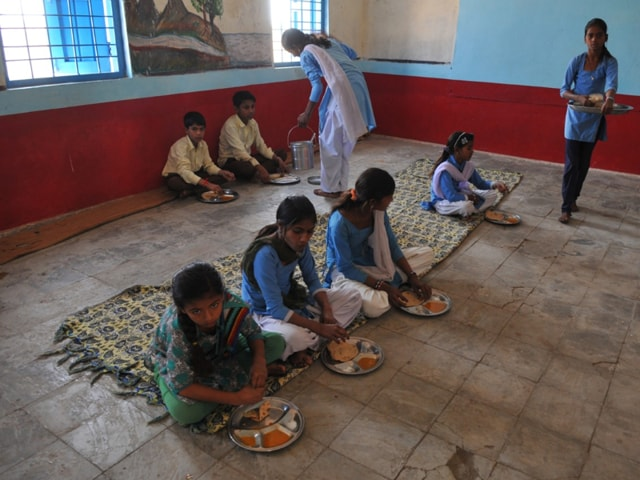 School kids eat chapati and dal with salt in Mahudiya Dev village school in Agar.