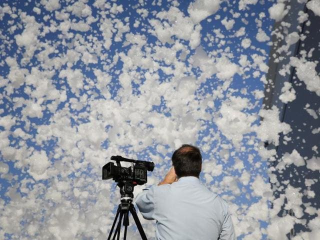 A TV cameraman films fire retardant foam blowing in the wind after a fire alarm malfunctioned in a hangar according to local media, near the San Jose airport in Santa Clara, California, US on Friday.