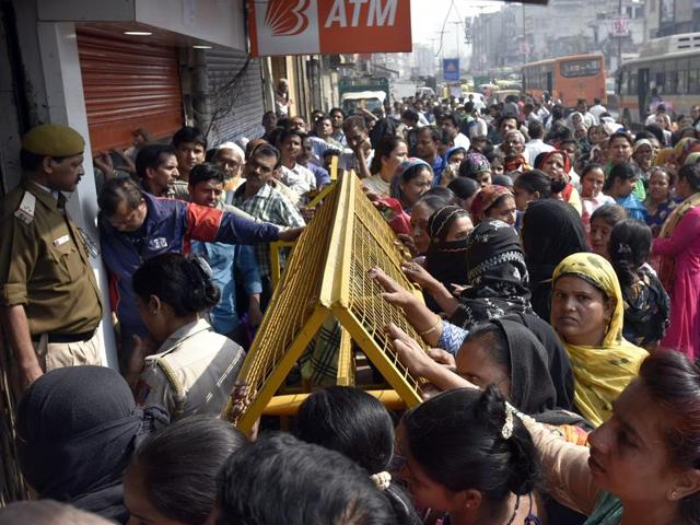 People gather outside a bank at Paharganj in New Delhi on Friday.