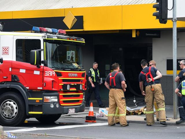 Emergency service workers are seen at a branch of the Commonwealth Bank after a fire injured customers in Melbourne, Australia.