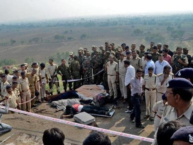 Police officers and Special Task Force soldiers stand beside the bodies of suspected SIMI members, on the outskirts of Bhopal.