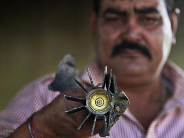 A villager displays a mortar shell fired from the Pakistan side, at a residential area near in Pallanwala sector, of Jammu and Kashmir on Tuesday.