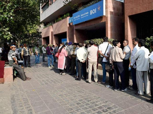 People stand in a queue to deposit/ exchange their old notes outside a bank in New Delhi on Saturday.
