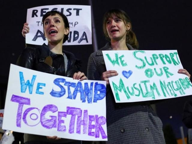 Demonstrators hold signs during a protest against President-elect Donald Trump and in support of Muslims residents in downtown Hamtramck, Michigan, US.