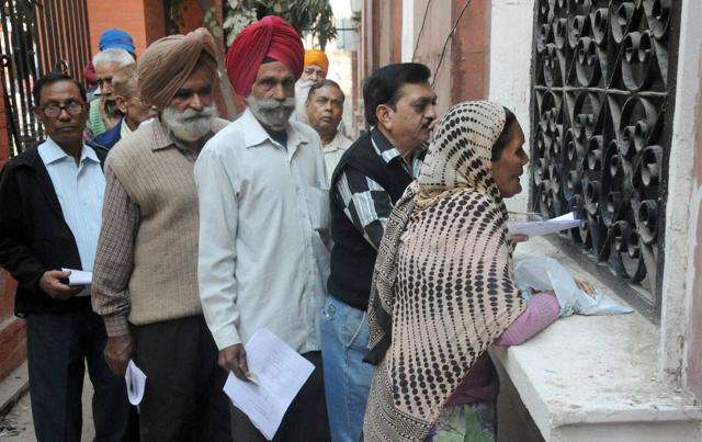 People exchange notes at a bank in Amritsar.