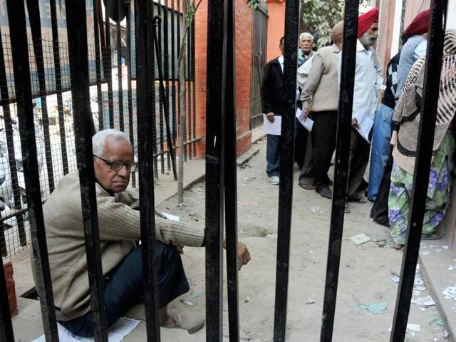 An elderly man sits as others stand in queue outside a SBI branch to exchange old notes, in Amritsar on Saturday.