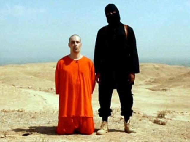 File photo showing Islamic State member before beheading a civilian. The Islamic State affiliate in Egypt says it has beheaded two men that it mistakenly described in a statement as priests.