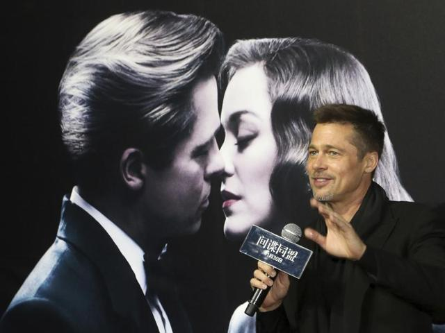 Actor Brad Pitt gestures to his fans as he attends a premiere of director Robert Zemeckis' new film Allied in Shanghai.