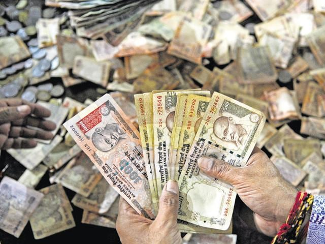 Temple priests at Sanatan Dharm Temple in sector 19 were seen checking Rs 500 and Rs 1000 notes in the donation box of the temple, in Noida, India