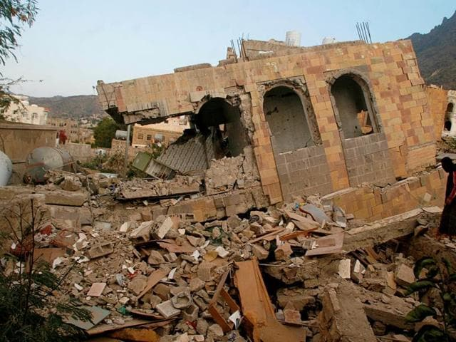 A man walks on the rubble of a house destroyed during recent battles between Houthi fighters and pro-government fighters.